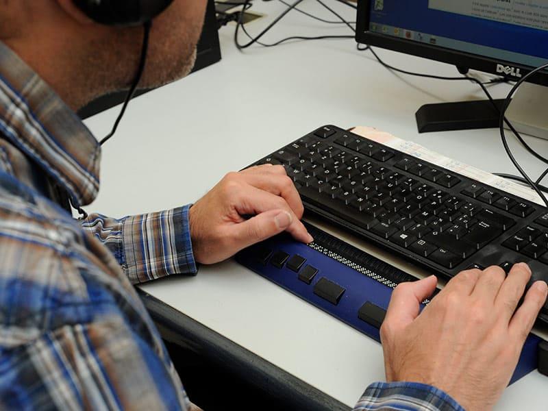 Photo d'un salarié utilisateur d'un afficheur braille